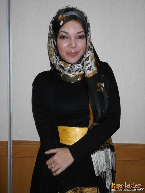 Dewi Sandra dengan balutan busana warna hitam yang diikat dengan selendang kuning emas di pinggangnya. Image via kapanLagi.