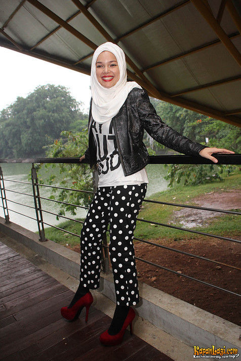 Dewi Sandra dengan jaket kulit dan celana polkadot. Image via KapanLagi.com