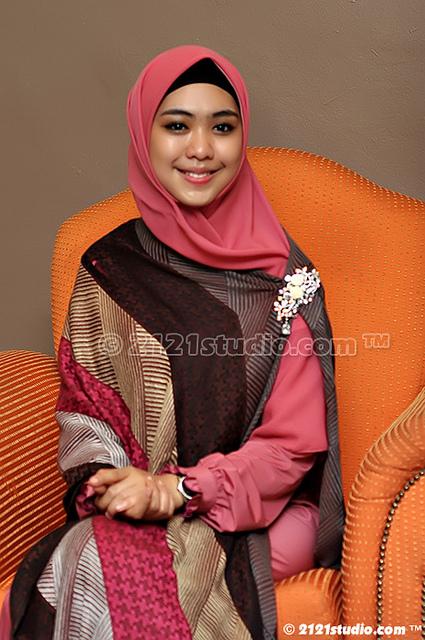 Okky Setiana Dewi mengenakan hijab segiempat dan Pashmina motif sebagai penutup dada.