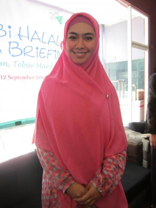 Okky Setiana Dewi mengenakan hijab segiempat polos, dan gamis bermotif.